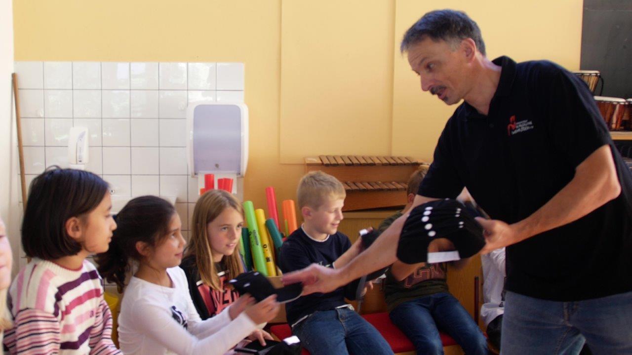 1. Vorsitzender Hubert Breisinger überreicht den Schülern Mützen des Fördervereins.