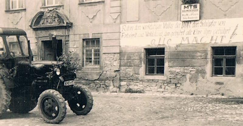 """MTS """"Maschinen- und Trecker-Schau"""" mit plakativer Wandaufschrift am """"Herrenhaus"""" in Branderoda: """"Ruhm dem werktätigen Volke der DDR dem Schöpfer von Fortschritt und Wohlstand, ihm gebührt alle Ehre ihm gebührt alle Macht!"""""""