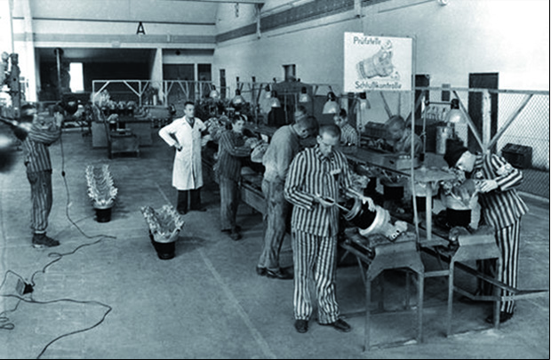 BMW-Werkmeister Eisenbart (in weissem Arbeitmantel)  mit KZ-Häftlingen 1943 in der Zylinderkopfmontage im BMW-Werk Allach.